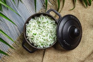 boiled rice with herbs in a pan on a wooden table - Салат из крабовых палочек с рисом