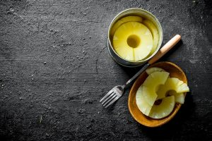 canned pineapples on a plate with a fork on black rustic background - Салат из крабовых палочек с ананасами и сыром