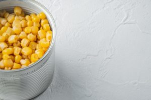 canned sweet corn in can on white background with copy space for text - Салат из крабовых палочек с рисом