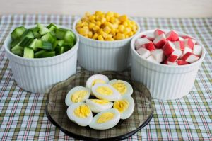 many ingredients for the salad sweet corn cucumber crab meat quail eggs on a light background - Салат из крабовых палочек с огурцами