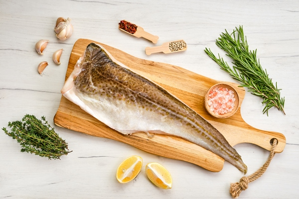 top view of fresh frozen cod carcass on wooden cutting board - Архангельский салат из трески