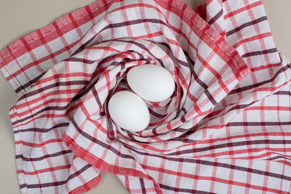 two fresh chicken white eggs on tablecloth - Архангельский салат из трески